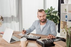 Sound producer working with mpc pads. Happy concentrated sound producer working with mpc pads at office Royalty Free Stock Image