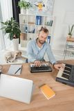 Sound producer working with mpc pads. High angle view of sound producer working with mpc pads while his dog laying on floor Stock Photos