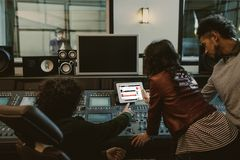 sound producers using tablet together at recording studio with soundcloud website stock photos