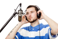 Sound recording. Young guy with a beard, writes a song with headphones and a microphone, isolated on white background Stock Photography