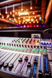 Sound recording studio mixer desk at a concert: professional music recording. Close up of a professional recording mixer desk, concert with lights in the blurry stock image