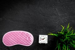 Sound sleep concept. Sleep mask, plant, alarm clock on black background top view copyspace Royalty Free Stock Images