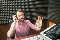 Sound technician gesturing start the show. Hispanic sound engineer gesturing ok sign to start the show at radio station Stock Photography