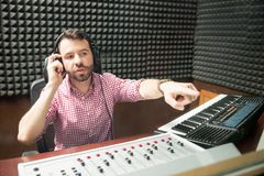 Sound technician gesturing to correct the mic position Royalty Free Stock Photography