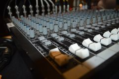 Soundboard control panel. Close up of control knobs and sliders on audio soundboard panel royalty free stock images