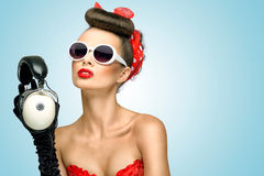 Sounds of glamour. The retro photo of a cute pin-up girl in sunglasses with vintage music headphones Stock Photos