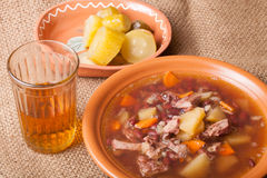 Soup with bean and potato, salty cucumbers and moonshine on a sa Stock Images