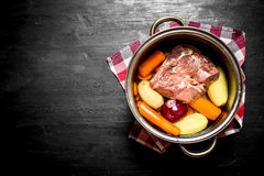 Soup with beef, carrots and fresh potatoes in the pan. On a black wooden background Stock Image