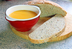 Soup in a bowl and fresh homemade bread. Stock Images