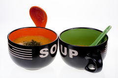 Soup bowls. Two bowls of hot soup with spoons royalty free stock photo