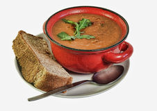 Soup and bread. A red bowl of soup, presented on a white plate with a thick slice of home made bread Stock Photography