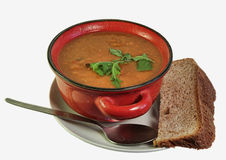 Soup and Bread. A red bowl of soup presented on a white plate, with a thick slice of home made bread and a spoon Royalty Free Stock Images