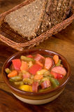 Soup and bread. Soup with vegetables, sausage and the rye bread Stock Image