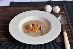Soup with carrots, mushrooms and sour cream. Soup with carrots, mushrooms and sour cream on a white plate and brown table top Royalty Free Stock Photos