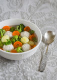 Soup with chicken meat balls, potatoes, broccoli and carrots in a white bowl Stock Images