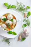 Soup with chicken meatballs and vegetables on white wooden background Royalty Free Stock Photo