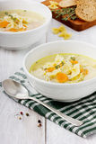 Soup chicken in a white bowl with spoon. On a white wooden table Stock Photo