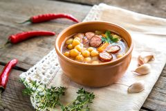 Soup with chickpeas and smoked sausage. On the wooden table Stock Photo