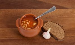 Soup in clay pot with bread and garlic Royalty Free Stock Photo