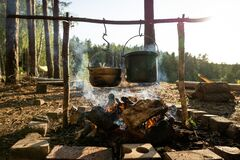 Homemade campfire cooking tools wiht large casseroles over a campfire while hiking.