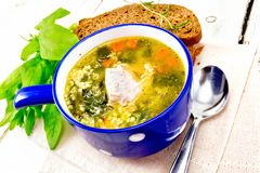 Soup with couscous and spinach in blue bowl on board royalty free stock photos