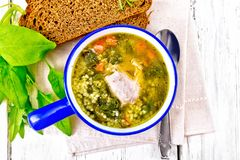 Soup with couscous and spinach in blue bowl on board top royalty free stock image