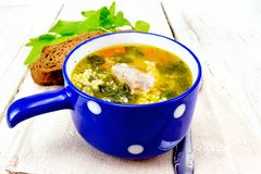 Soup with couscous and spinach in blue bowl on napkin royalty free stock image