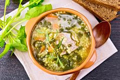 Soup with couscous and spinach in clay bowl on board top royalty free stock photography