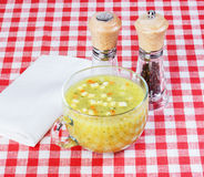 Soup with croutons in a glass mug of broth, pepper, salt shaker, Stock Photos