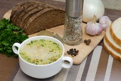 Mushroom soup with croutons in a white dish is on a wooden table Royalty Free Stock Photo