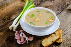 Soup garlic with toasted croutons. On wood table Royalty Free Stock Photos