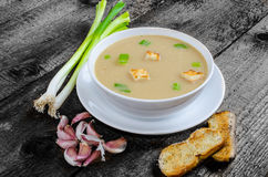 Soup garlic with toasted croutons. On wood table Royalty Free Stock Photography