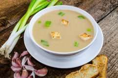 Soup garlic with toasted croutons. On wood table Stock Photo