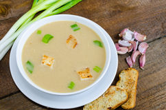 Soup garlic with toasted croutons. On wood table Royalty Free Stock Image