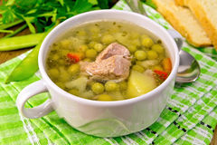 Soup from green peas with meat on green napkin Royalty Free Stock Image