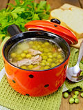 Soup from green peas with meat in red bowl and bread on board Royalty Free Stock Photography