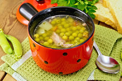 Soup from green peas with meat in red bowl on napkin Royalty Free Stock Image