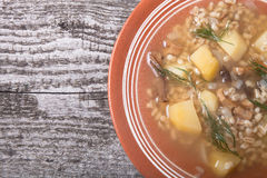 Soup with grits, mushrooms, potatoes and dill in a bowl on old w Royalty Free Stock Image