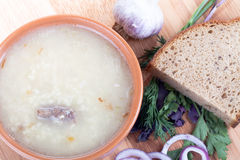 Soup kulesh of millet grains and meat with bread, garlic and her Royalty Free Stock Photography