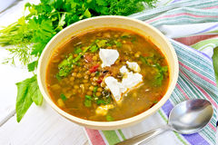 Soup lentil with spinach and cheese in yellow bowl on board Stock Photography