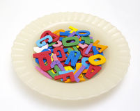 Soup of letters. Plate with rubber letters in white bottom Royalty Free Stock Photos