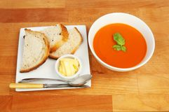 Soup lunch on a table. Bowl of tomato soup with bread and butter on a plate on a wooden tabletop, top view Royalty Free Stock Images