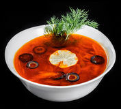 Soup with meat, olives, herbs and lemon in bowl, isolated on black background, homemade food. Royalty Free Stock Image