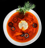 Soup with meat, olives, herbs and lemon in bowl, isolated on black background, homemade food. Royalty Free Stock Photos