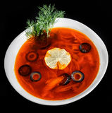 Soup with meat, olives, herbs and lemon in bowl, isolated on black background, homemade food. Royalty Free Stock Images