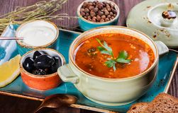 Soup with meat, olives, herbs, lemon, sour cream in bowl, black bread and spices on dark wooden background, homemade food. Traditional Russian soup - solyanka royalty free stock images