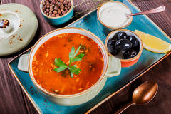 Soup with meat, olives, herbs, lemon, sour cream in bowl, black bread and spices on dark wooden background, homemade food Royalty Free Stock Photos
