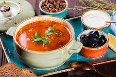 Soup with meat, olives, herbs, lemon, sour cream in bowl, black bread and spices on dark wooden background, homemade food. Stock Photo