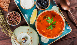 Soup with meat, olives, herbs, lemon, sour cream in bowl, black bread and spices on dark wooden background, homemade food. Royalty Free Stock Photos