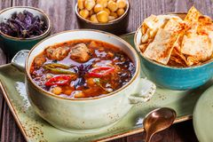 Soup with meat, oregano, chickpeas, peppers and vegetables served with crackers and bread on plate on dark wooden background. Stock Image